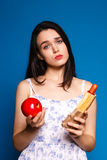 Difficult choice of food, a beautiful brunette with Vegetables and hotdog Royalty Free Stock Image