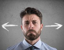 Difficult choices of a businessman. concept of confusion. Confused businessman looking a wall with directional arrows. concept of confusion Stock Photography