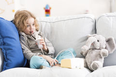 Difficult day for an asthmatic child. Little boy with worried face sitting among soft cushions on a sofa, breathing with an inhalator royalty free stock images