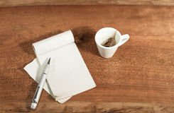 Difficult decision with a cup of coffee. Empty cup of coffee with some objects in disorder on the table of work Stock Images