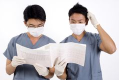 Difficult Diagnosis. Two doctors struggle looking at an ecg printout Royalty Free Stock Photography