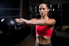 Difficult exercise. Sweaty young woman lifting heavy kettlebell in stretched arms during cross training practice Royalty Free Stock Photos