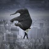 Difficult job concept. Portrait of businessman carrying heavy elephant while walking on the rope over a big city Stock Photo