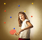 Difficult match. Little girl with astonished expression playing ping pong with many balls Stock Image