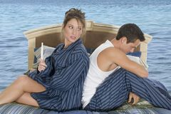 Difficult moment. Young couple going through a difficult intimate situation, in bed, over an ocean background Stock Photo