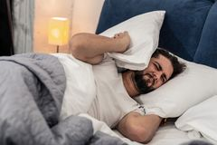 Cheerless unhappy man wanting to stay in bed. Difficult Monday. Cheerless unhappy man wanting to stay in bed while hearing the alarm clock in the morning royalty free stock images