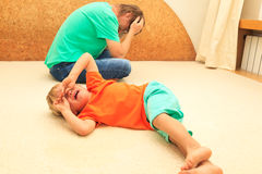 Difficult parenting. Baby is crying, father is tired Stock Photography