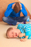 Difficult parenting. Baby is crying, father is tired Royalty Free Stock Images