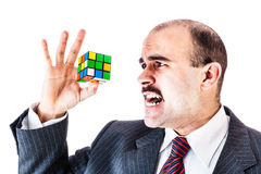 Difficult puzzle. Portrait of a businessman trying to solve a cube puzzle isolated over a white background Royalty Free Stock Photo