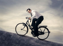 A difficult ride. A man riding a bike up a hill Royalty Free Stock Photos