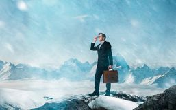 Difficult and risky business way concept. Young businessman with leather briefcase in the mountains in bad weather Royalty Free Stock Photo