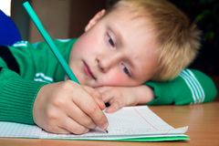 Difficult school homework. Tired boring boy doing his difficult school homework royalty free stock photo