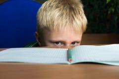 Difficult school homework. Tired boring boy don't want to do his difficult school homework stock photography