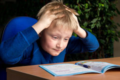 Difficult school homework. Tired boring boy don't want to do his difficult school homework stock image