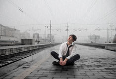 Difficult situation. Wet businessman sitting on the platform of a train station Royalty Free Stock Images