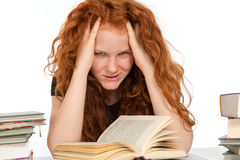 Difficult studies. Red-haired girl has difficult studies royalty free stock images
