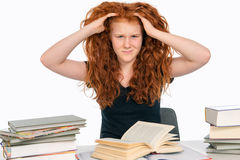 Difficult studies. Red-haired girl has difficult studies stock image