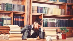 Difficult subject, confusing question, study, education, hard work, intellectual research concept. Man sits at table. With many books. Mature man has serious stock photography