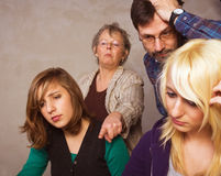 Difficult task. Two teenager girls doing their homework together with their parents stock image