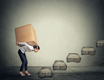 Difficult task concept. Woman carrying heavy box upstairs. Difficult task perspective concept. Young slim woman entrepreneur carrying large heavy box on her back Stock Photo