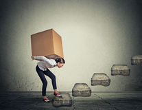 Difficult task concept. Woman carrying heavy box upstairs. Difficult task perspective concept. Young slim woman carrying large heavy box on her back upstairs Stock Photo