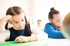 Difficult task. Schoolgirl puzzled by the task. She is sitting at the desk at school Royalty Free Stock Photos