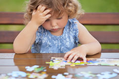 Difficult task. Tired child playing jigsaw with serious face. Blonde unhappy toddler girl, solving puzzle on a table, hard difficult task. Early education and royalty free stock images