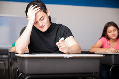 Difficult test in high school. Portrait of an attractive teen having trouble solving a test in high school Stock Photos