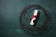 Difficult to achieve. Certificate with ribbon surrounded by barbwire Stock Photo
