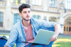 Difficult university. Cute male student holding a laptop and rea. Ding a book and looking away while sitting on the grass near the campus of the University at Royalty Free Stock Image