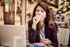 It is so difficult working with fever. Business woman in cafe sitting stock photo