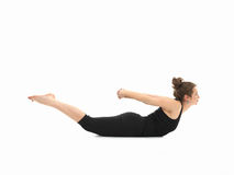 Difficult yoga posture. Young caucasian woman in lying yoga pose, side view, full body, dressed in black, on white background Royalty Free Stock Images