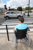 Daily difficulties. Young man using wheelchair in town Royalty Free Stock Image