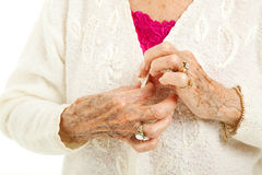 Difficulties of Arthritis. Senior woman\'s arthritic hands struggling to button her sweater Stock Images