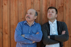 Difficulties in family relationships. The father-in-law and the son-in-law look puzzled upwards Royalty Free Stock Images