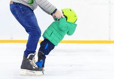 Difficulties of the first steps on skates. Child makes first steps on skates with assistance in ice rink Stock Photos