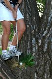 Difficutl Shot. A woman hits a golf ball from a tree Royalty Free Stock Photography