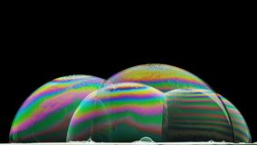 Diffraction phenomenon in some soap bubbles. Light diffraction phenomenon in some soap bubbles illuminated from below Stock Photo