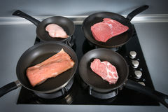 Diffrent kinds of meat on pans. Taken in a kitchen, used an external light from above Stock Images