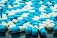 diffusion antibiotique blanc bleu de pilule de capsule sur le plateau de drogue d'acier inoxydable concept global de soins de san photos stock
