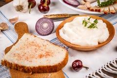 Diffusion de saindoux sur le pain cuit au four à la maison Images stock