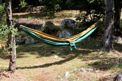 Diffusion en nylon d'hamac de sac de parachute entre deux arbres en parc local utilisé pour se reposer dans l'ombre de grands arb photos libres de droits