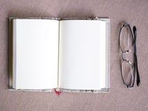 Diffusione aperta della pagina in bianco del libro con gli occhiali sulla tavola Fotografia Stock