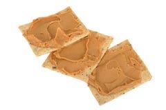 Diffusione del burro di arachidi sui cracker seminati Fotografia Stock