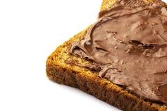 Diffusione della nocciola del cioccolato sul pane tostato del grano intero isolato fotografie stock