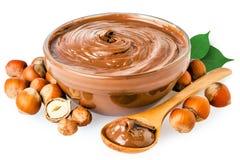 Diffusione della nocciola del cioccolato zuccherato con gli interi dadi isolati su bianco Fotografia Stock
