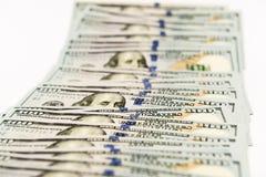 Diffusione di molte banconote di cento dollari sulla superficie di bianco Immagini Stock