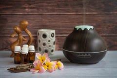 Diffusor Brown-ätherischen Öls mit Frangipaniblumen, Kerze und kleiner hölzerner Liebesstatue stockbild