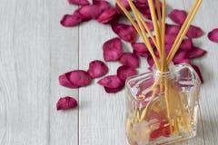 Difusor de Reed con fragancia en un tarro de cristal con los p?talos color de rosa imágenes de archivo libres de regalías