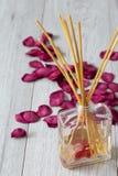 Difusor de Reed con fragancia en un tarro de cristal con los p?talos color de rosa fotografía de archivo